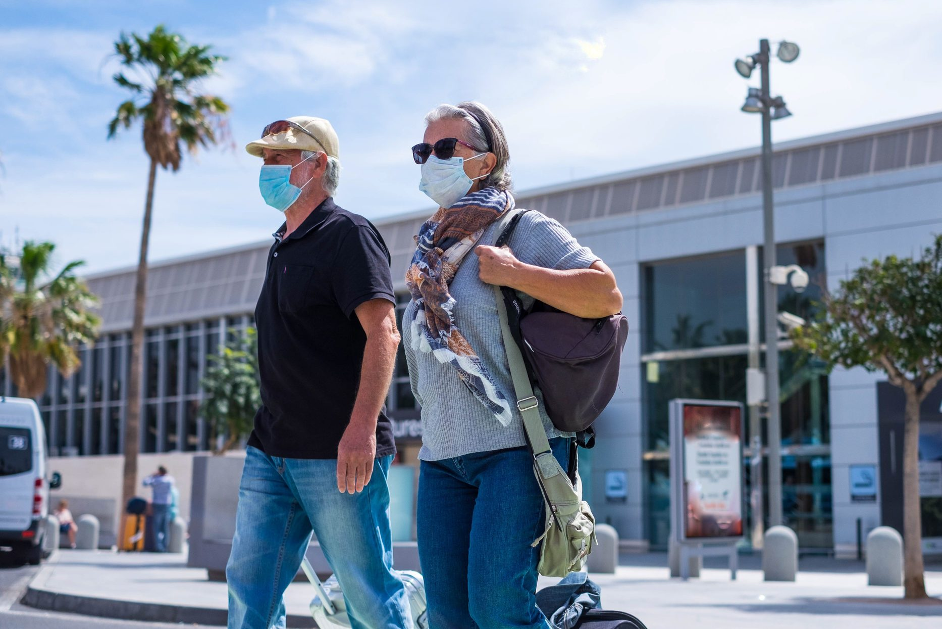 two senior walking with their baggage and wearing medical mask to prevent covid-19 or coronavirus or another type of virus or disease - safe travelers concept and lifestyle walking outdoor
