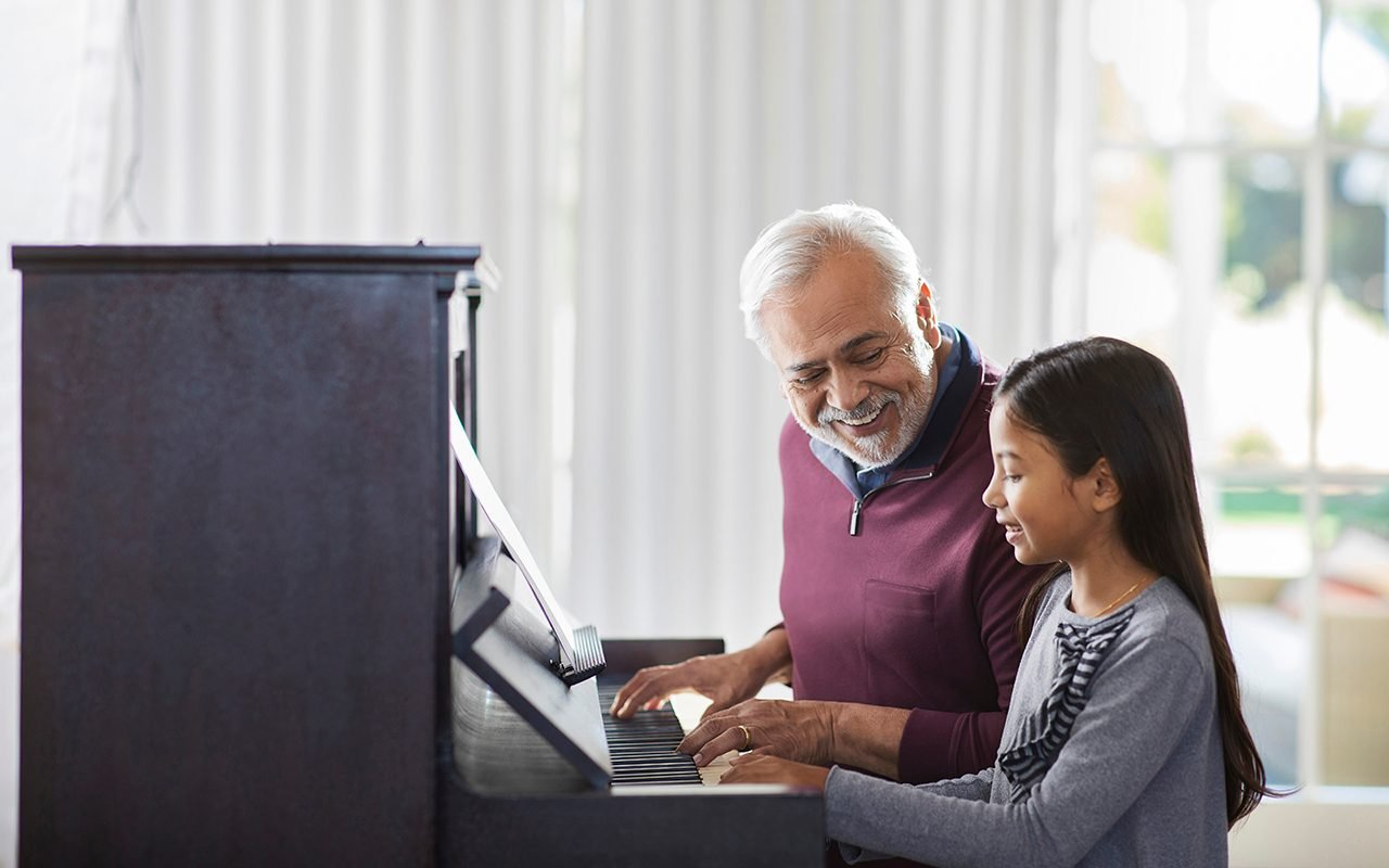 Senior man teaching a child to play the piano