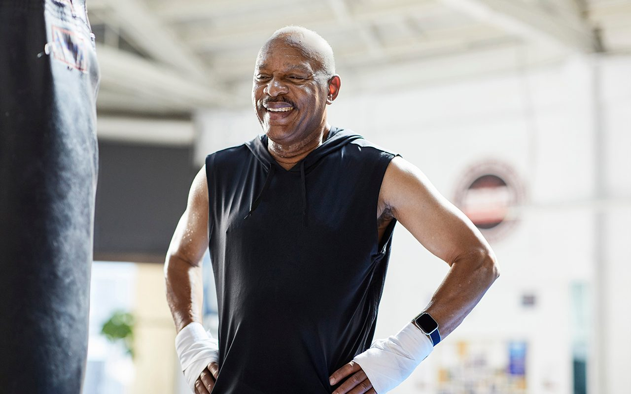 Senior man working out boxing at a gym