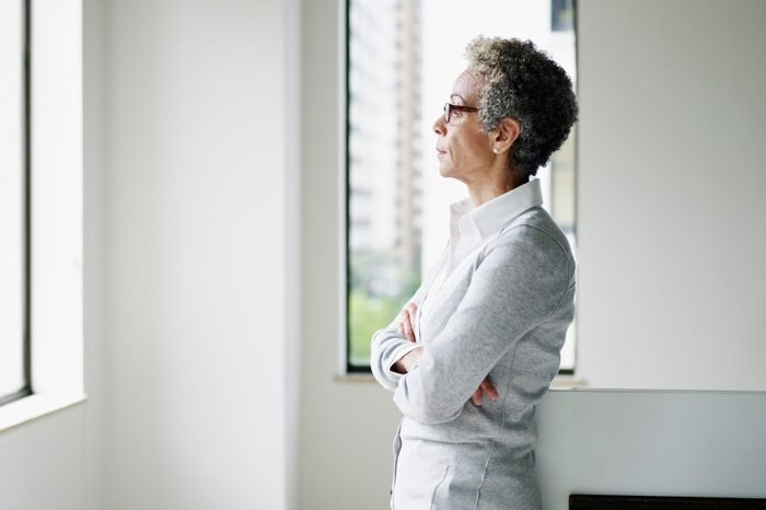 Mature businesswoman in office looking out window