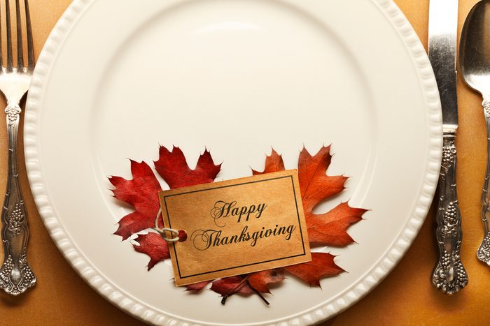 Thanksgiving Place Setting With Happy Thanksgiving Tag And Autumn Leaves