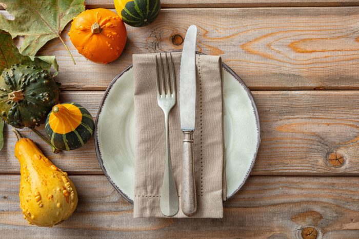 Thanksgiving flat lay with colorful pumpkins and place setting on rustic wooden table, copy space, top view