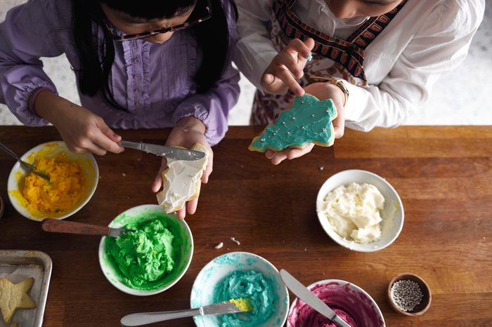 siblings decorating Christmas cookies together