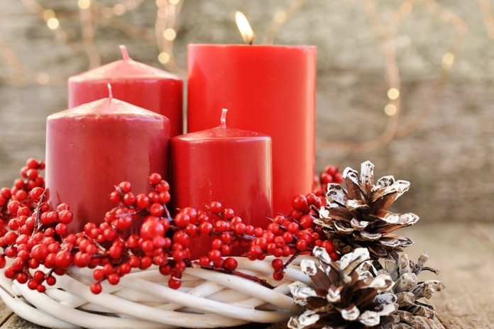 Four candles in a white wreath with red berries on a wooden rustic background with lights. advent calendar for Christmas.