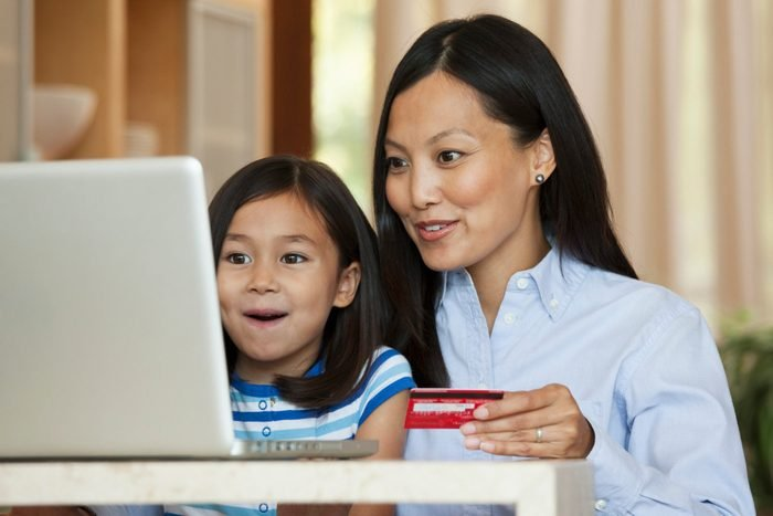 Mother and daughter using credit card online