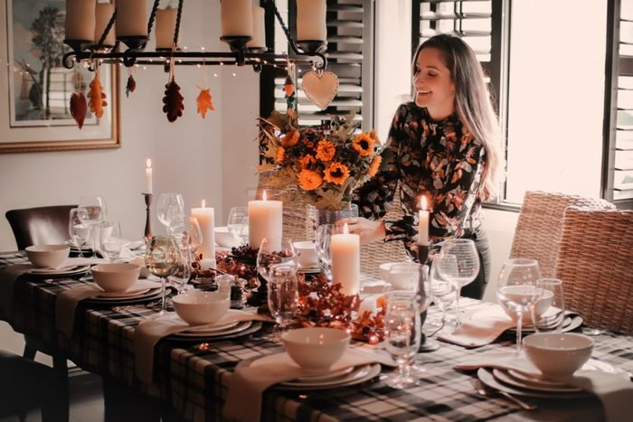 young woman setting the thanksgiving table with sunflowers and autumn decorations