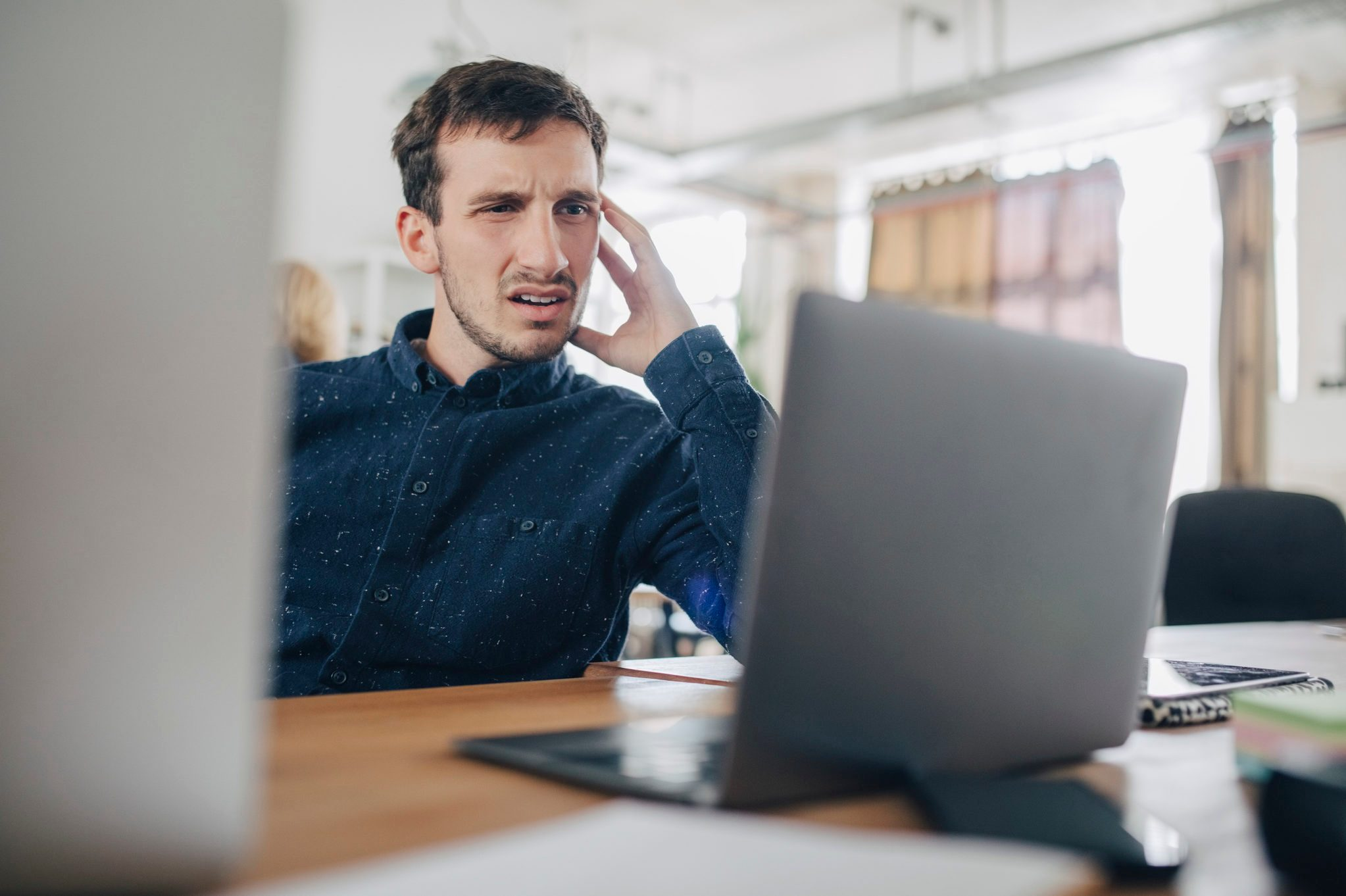 Confused businessman looking at laptop while sitting at desk in office