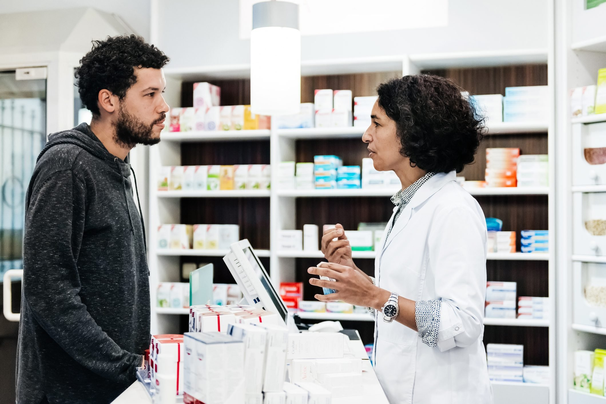 Pharmacist Assisiting Customer With Prescription Queries