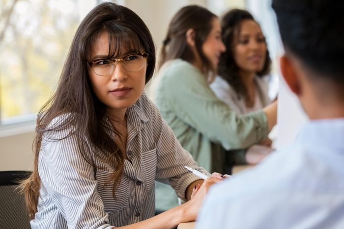 Young female creative professional listens to coworker