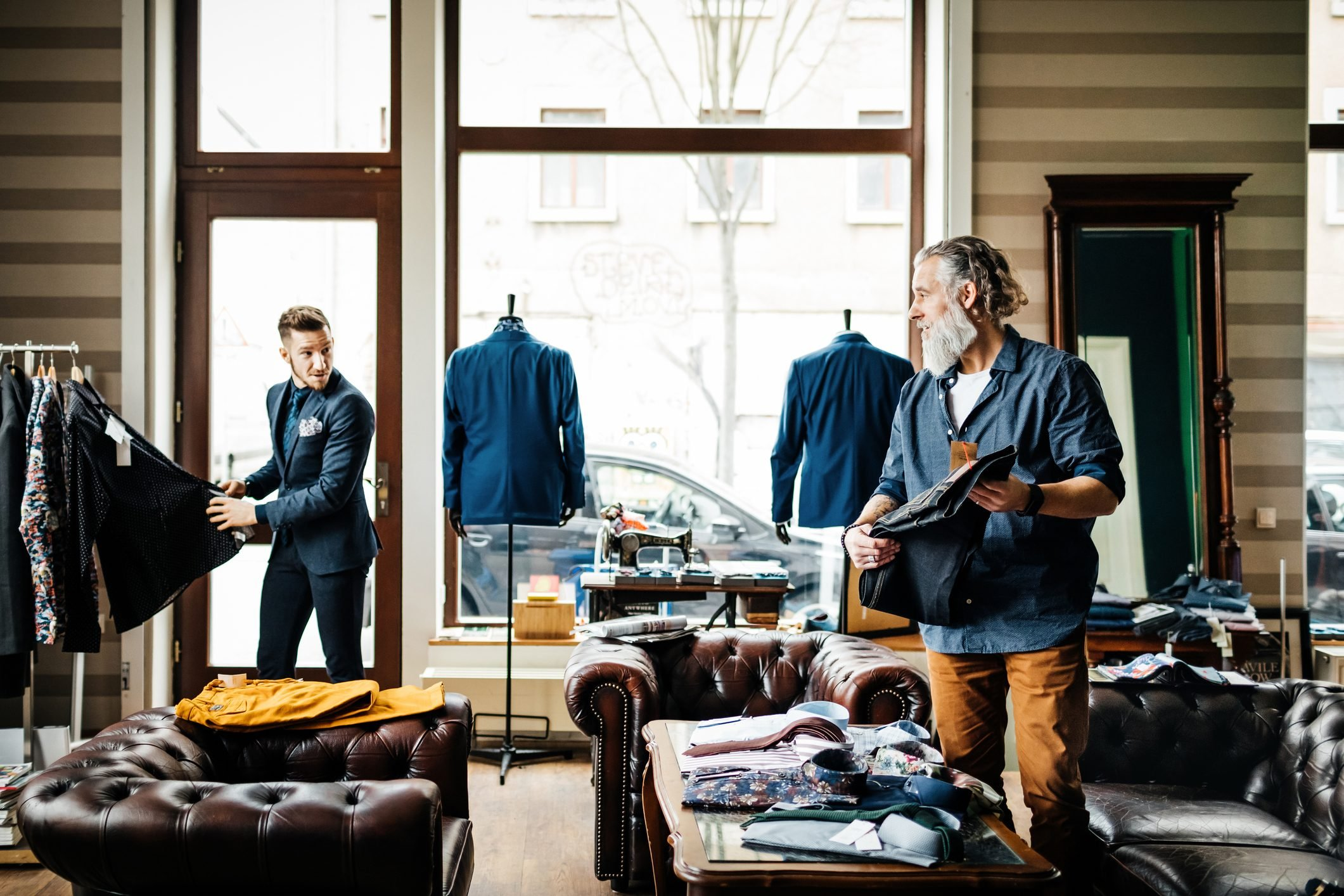 Retail Assistant Helping Man In Menswear Store