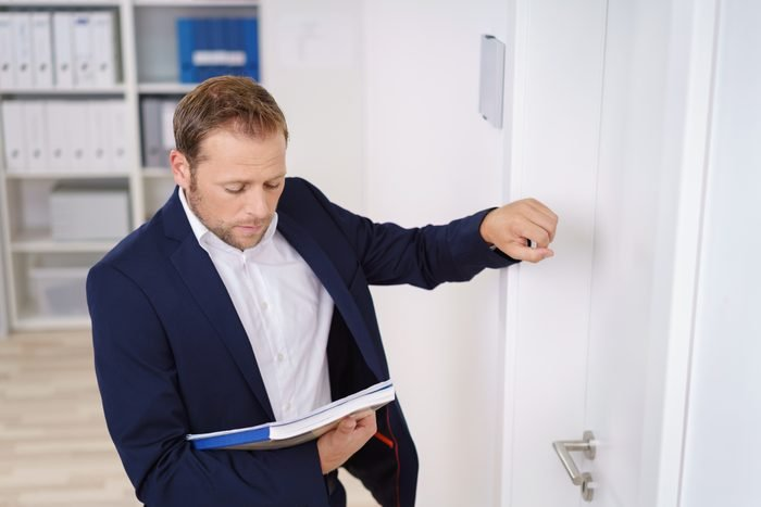 Young businessman knocking on the door of the boss