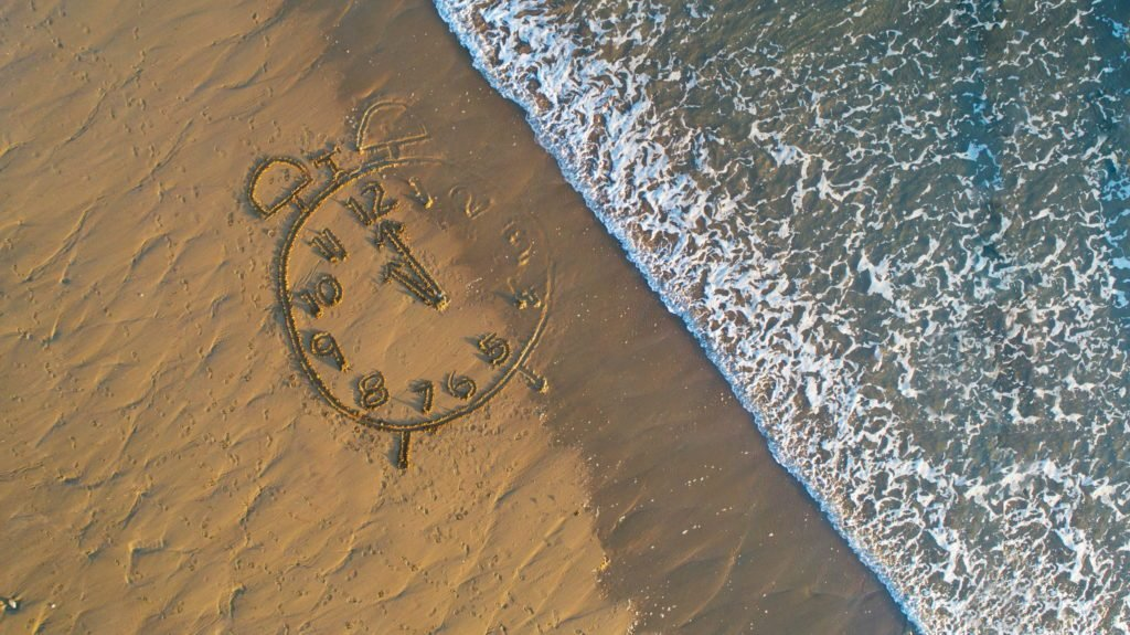 Clock drawn in sand at water's edge