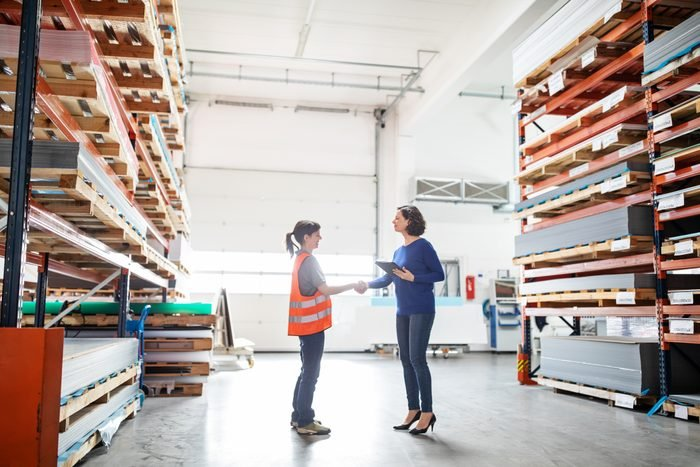 Businesswoman shaking hands with worker in large warehouse. Manager and worker handshake in storehouse