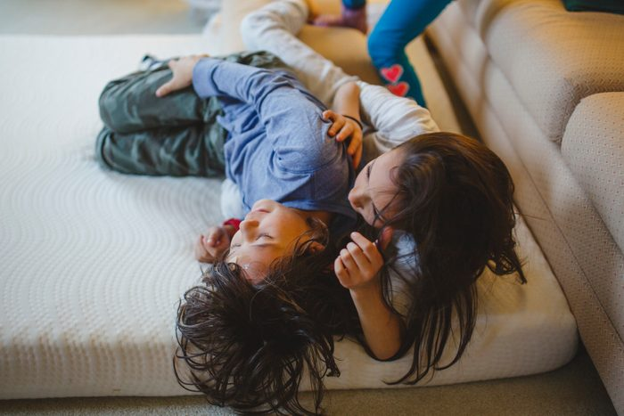 siblings playing and wrestling on a mattress at home