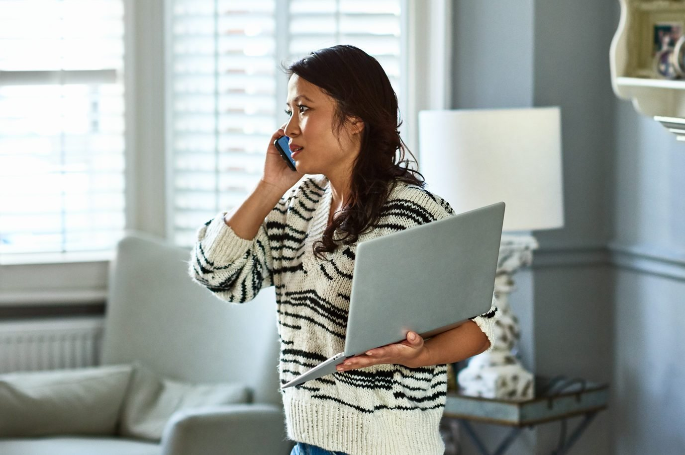 Woman holding laptop and listening on smartphone