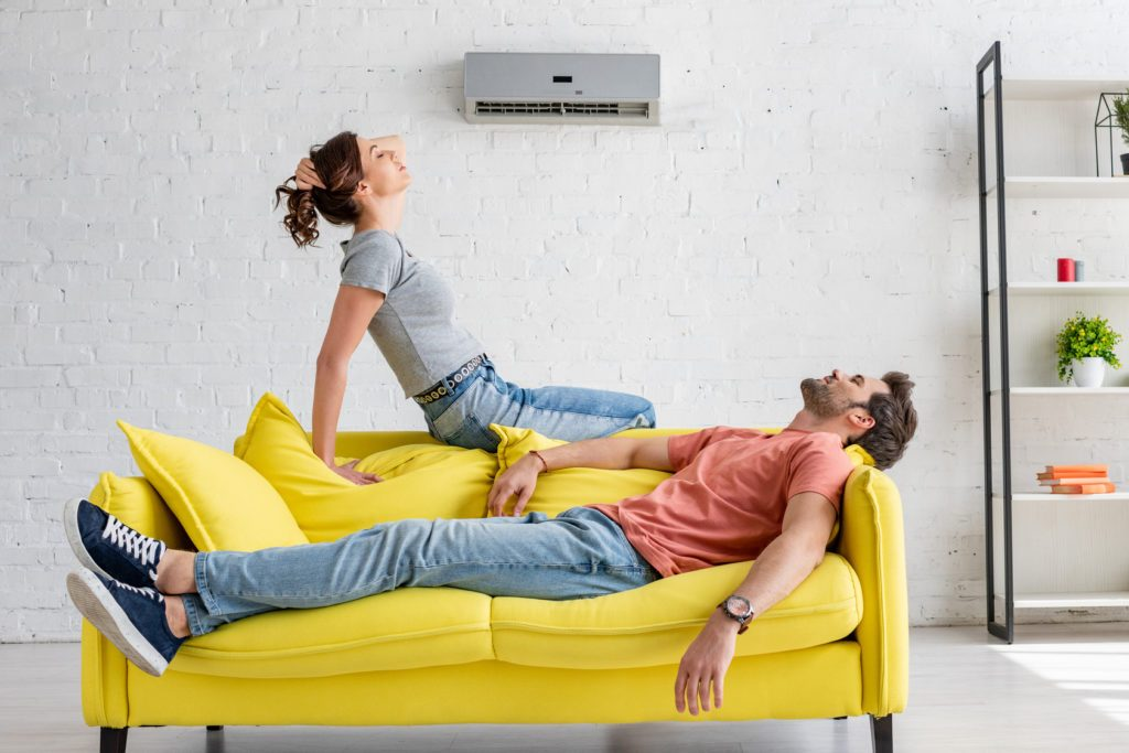 young man and woman resting on yellow sofa under air conditioner at home