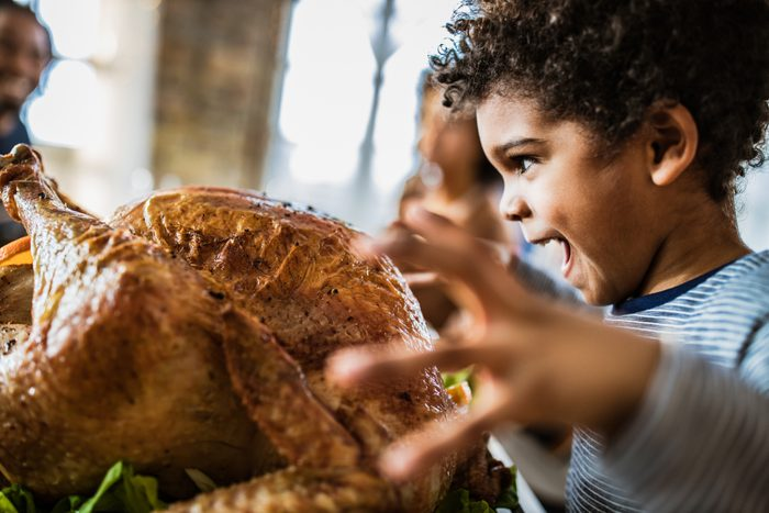 African American boy about to bite stuffed turkey on Thanksgiving day.