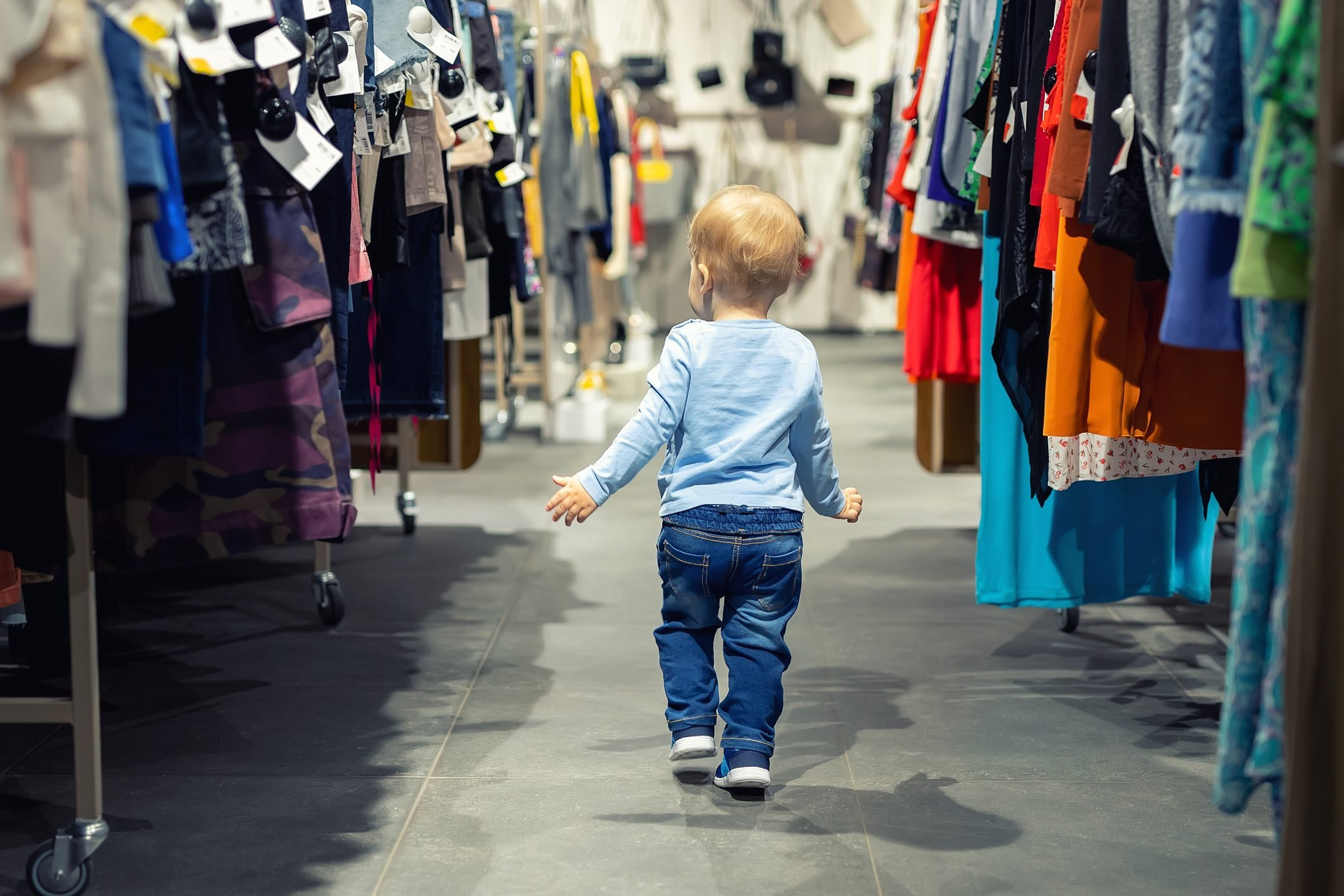Rear View Of Boy Amidst Clothes In Store