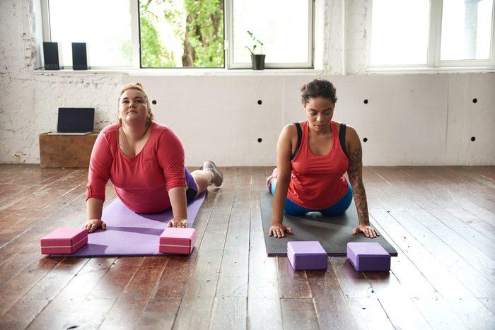 Calm fat women are doing yoga exercises