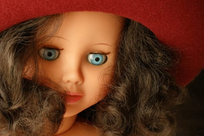 Cover doll wearing a red felt hat