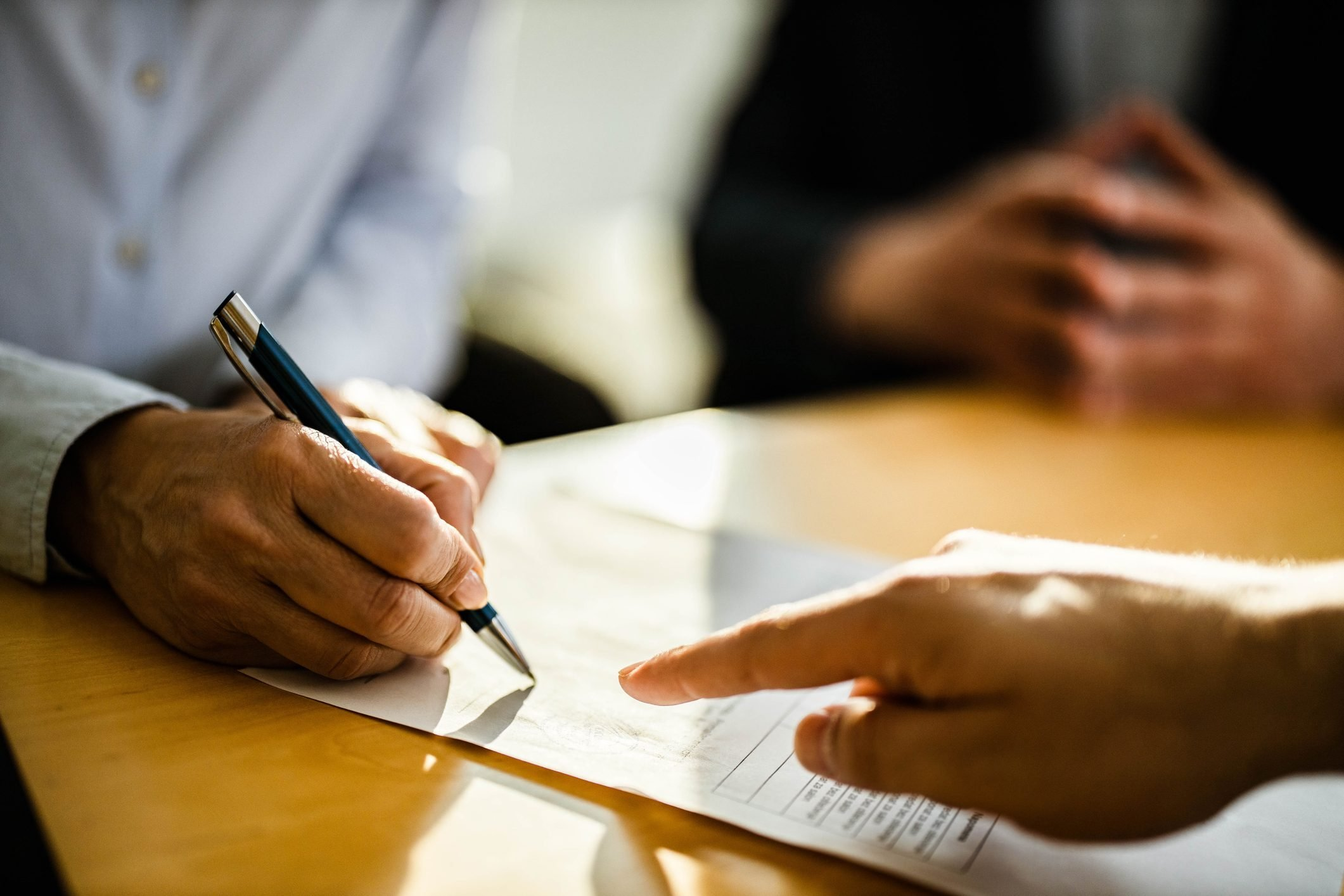 Close up of unrecognizable person signing a contract.