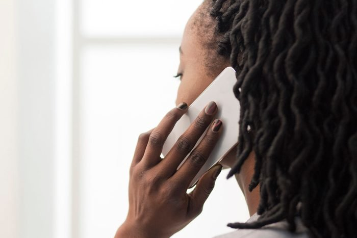 Unrecognizable Businesswoman Talking On Cellphone In Office, Closeup