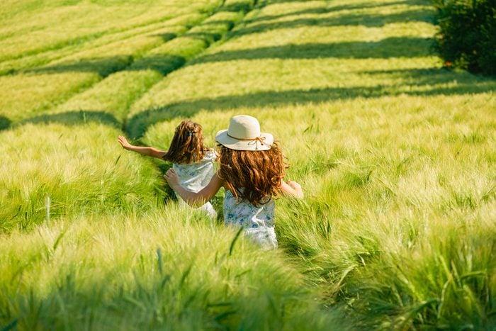 Playful, carefree girls running in sunny, idyllic rural green wheat field