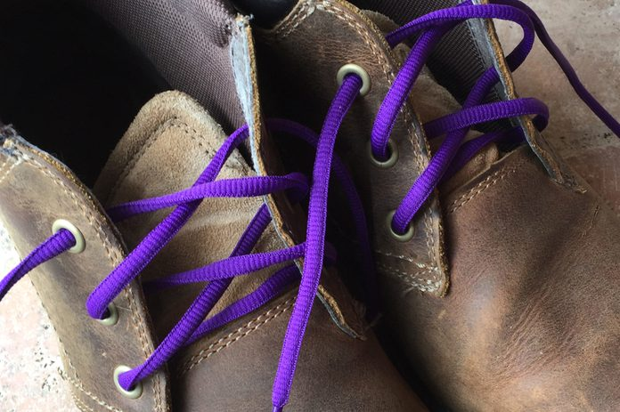 Image of second hand, brown leather work boots cutomized with purple shoe laces