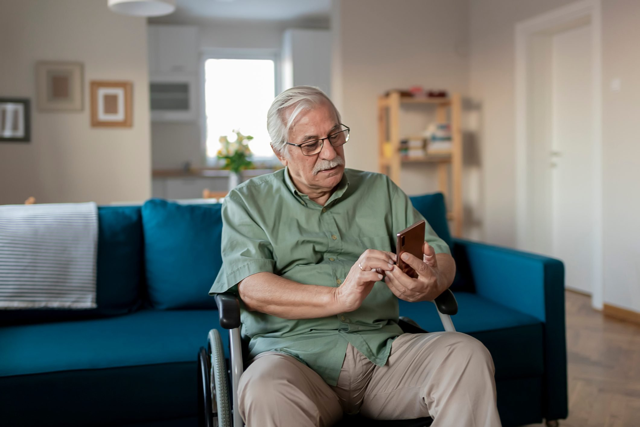 Handicapped Senior Man Sitting in a Wheelchair and Using a Smartphone