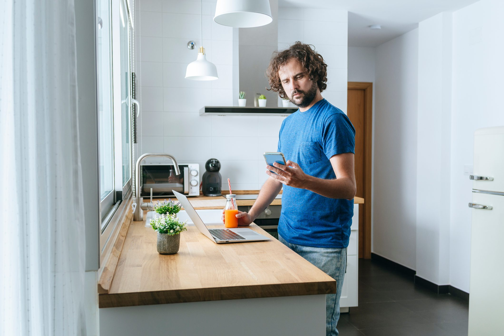 Man with smartphone and laptop in the kitchen