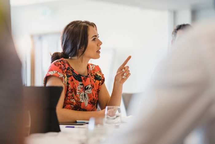 Confident young businesswoman explaining in work meeting