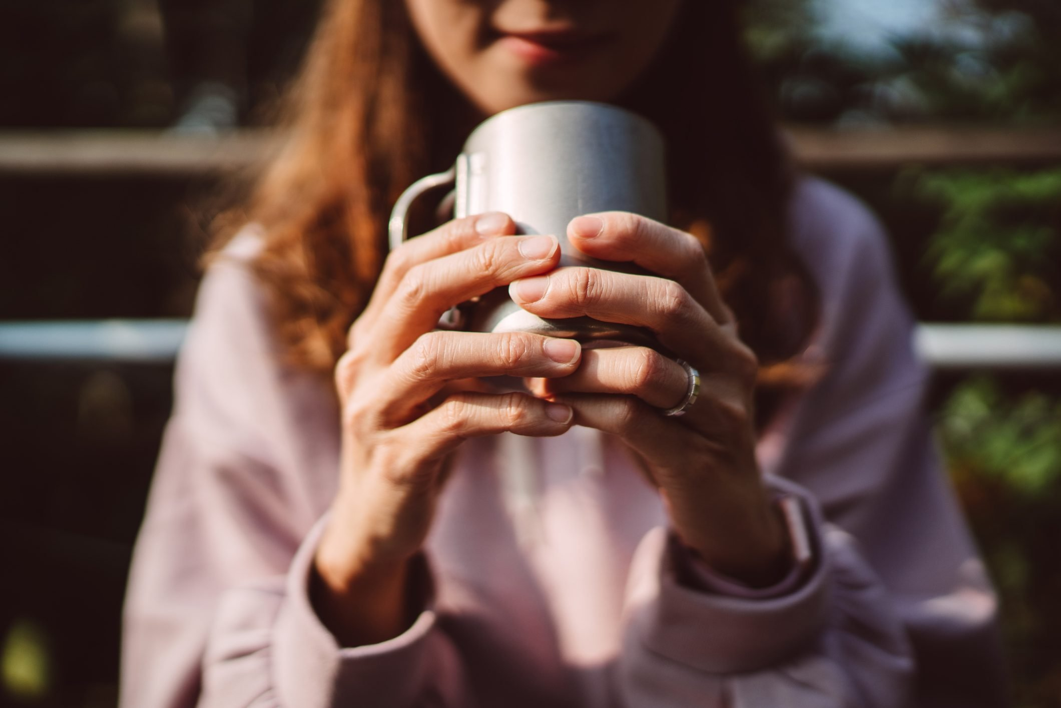 Close-up of lady's hands holding a reusable coffee cup in country side
