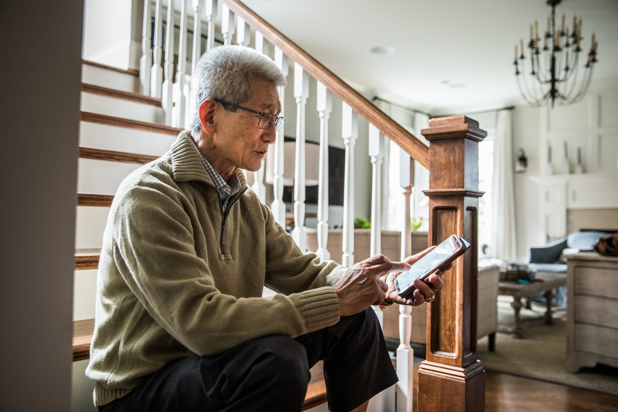 Senior man listening to music on laptop wearing headphones