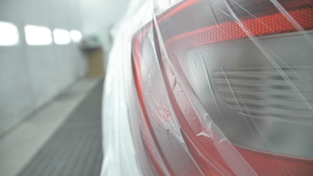 White car is standing in a spray booth covered with a transparent film. Ready to paint. Taillights