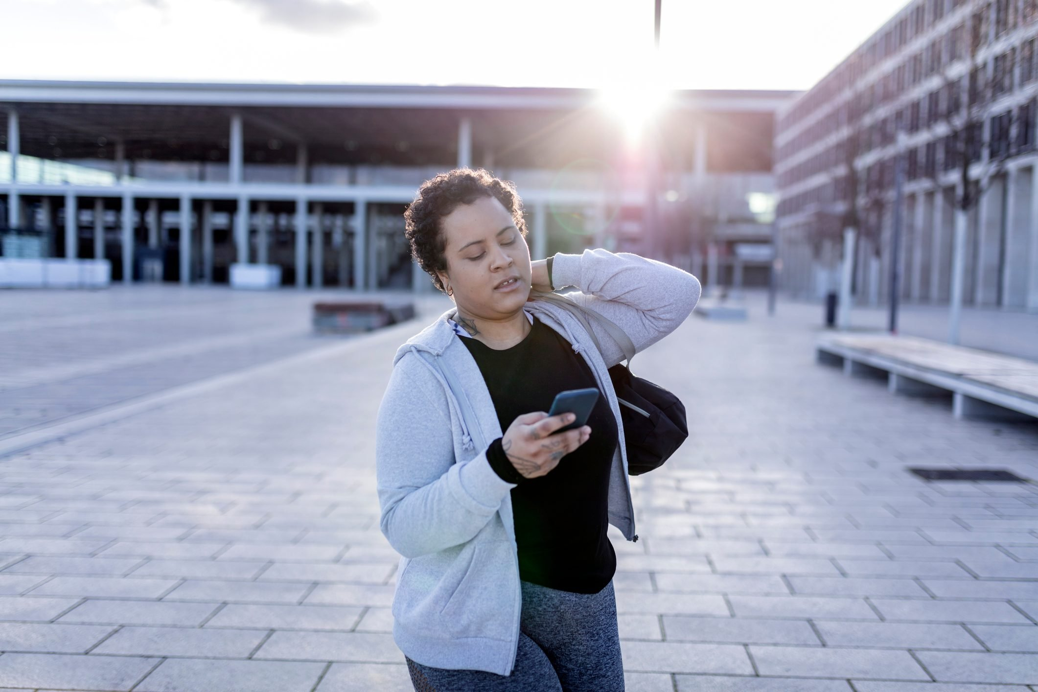 portrait of a young and curvy women with sports bag and mobile phone walking to her fitness club