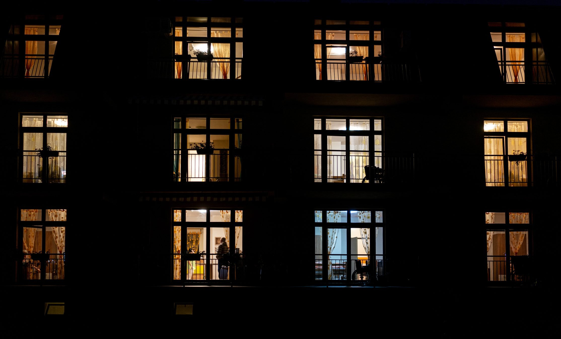 Illuminated windows of night house with people inside