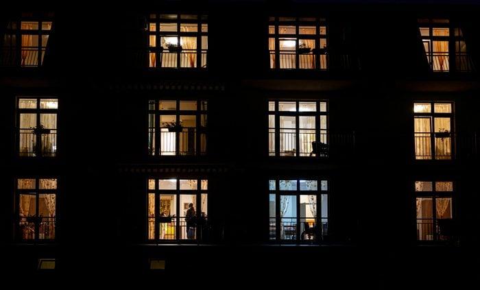Illuminated windows of night house with people inside