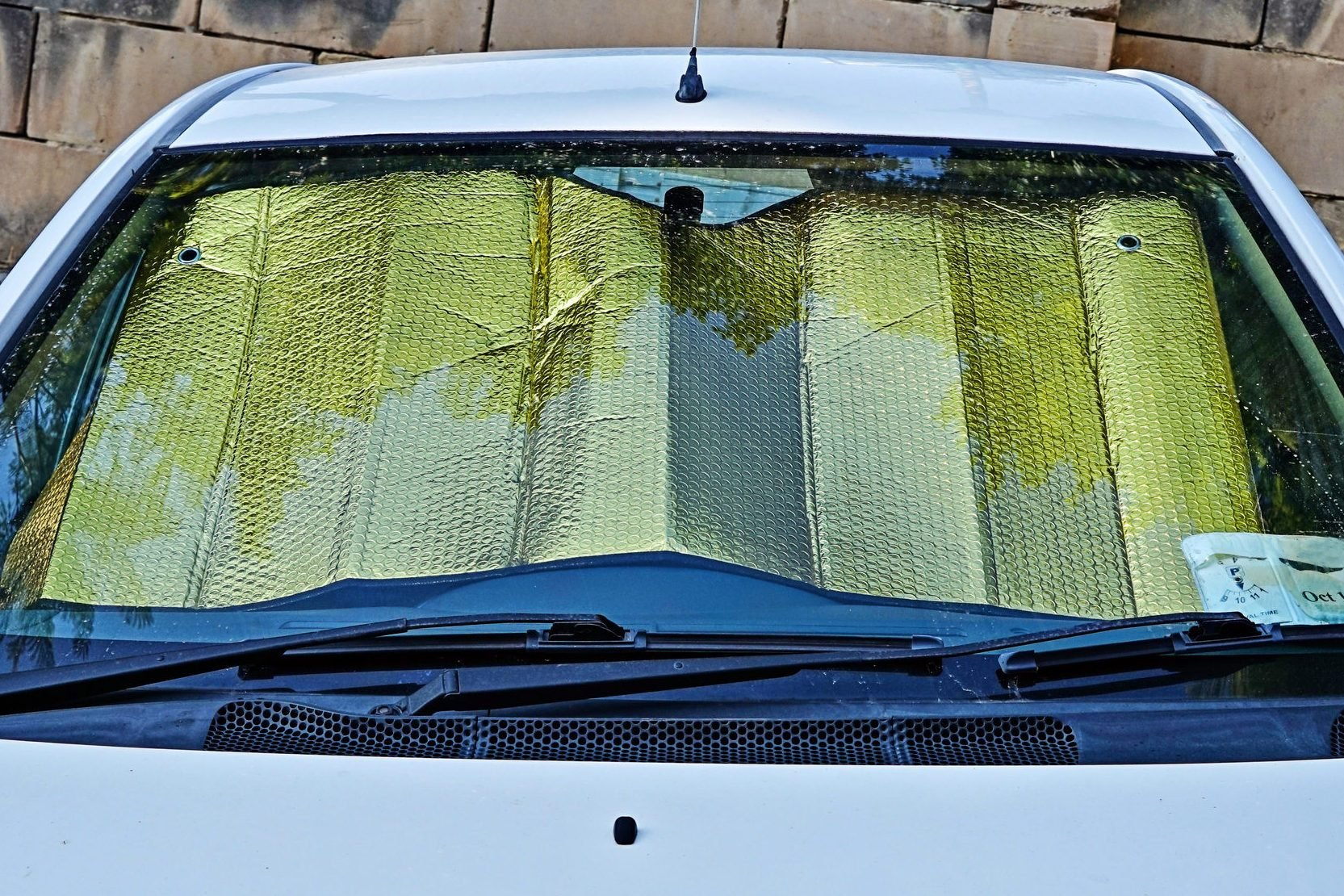 Windshield of car with protective reflective sunscreen surface inside car