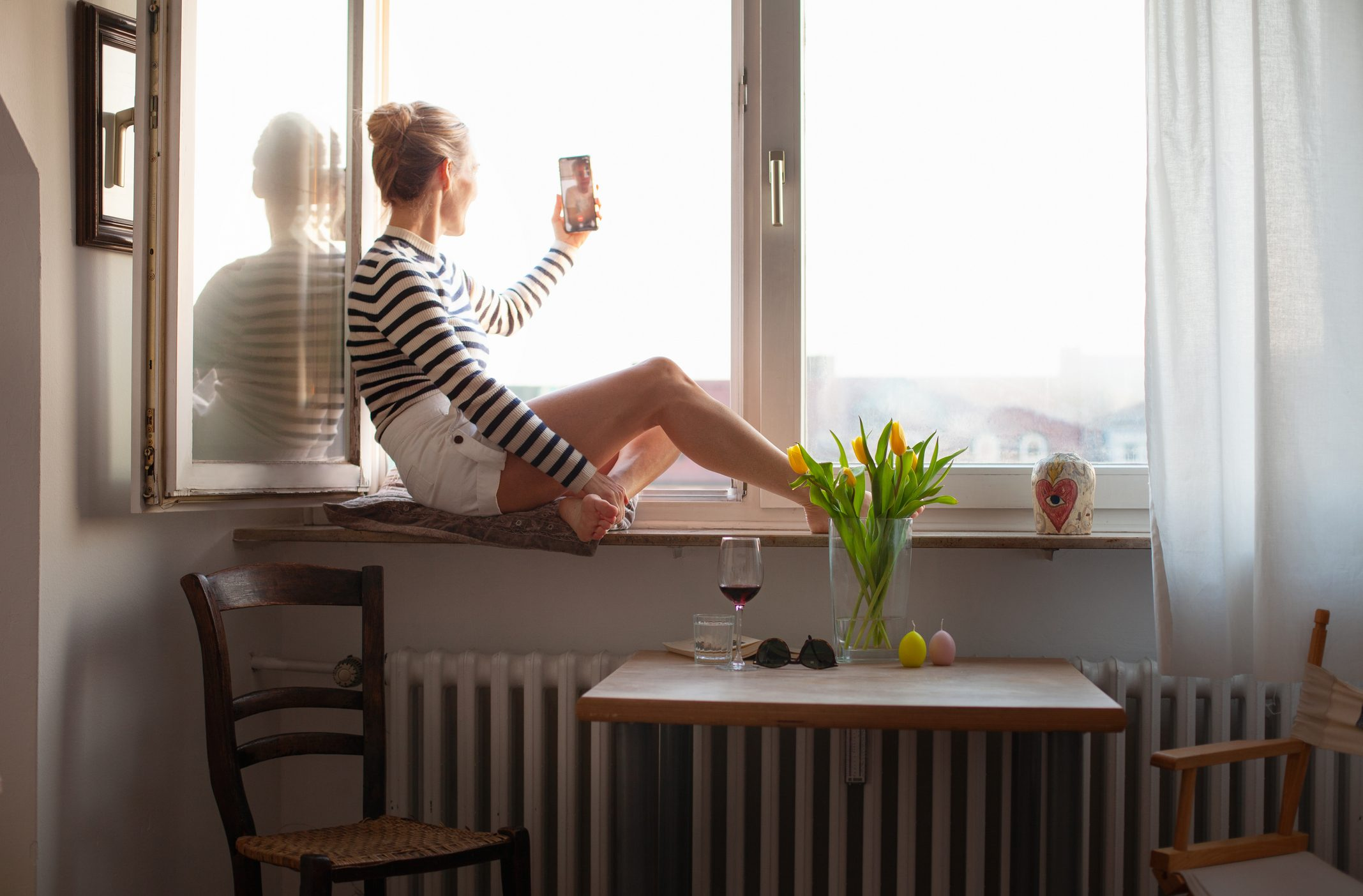Woman sitting on a windowsill, video chatting with family member