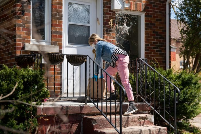 A woman wearing a surgical mask and protective gloves drops off bags of groceries onto the front steps of a small house.