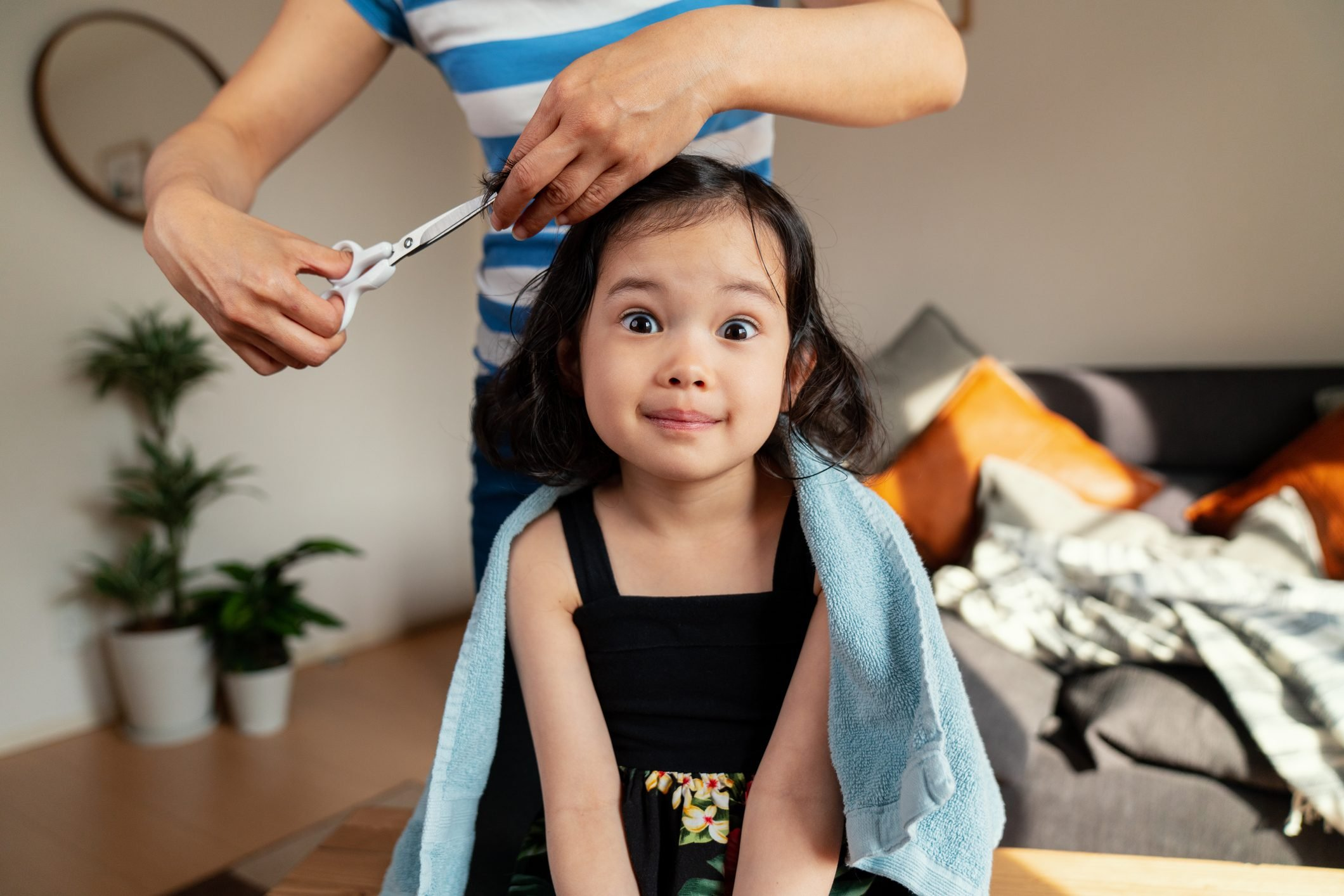 Young girl pulling a face whilst getting a haircut at home