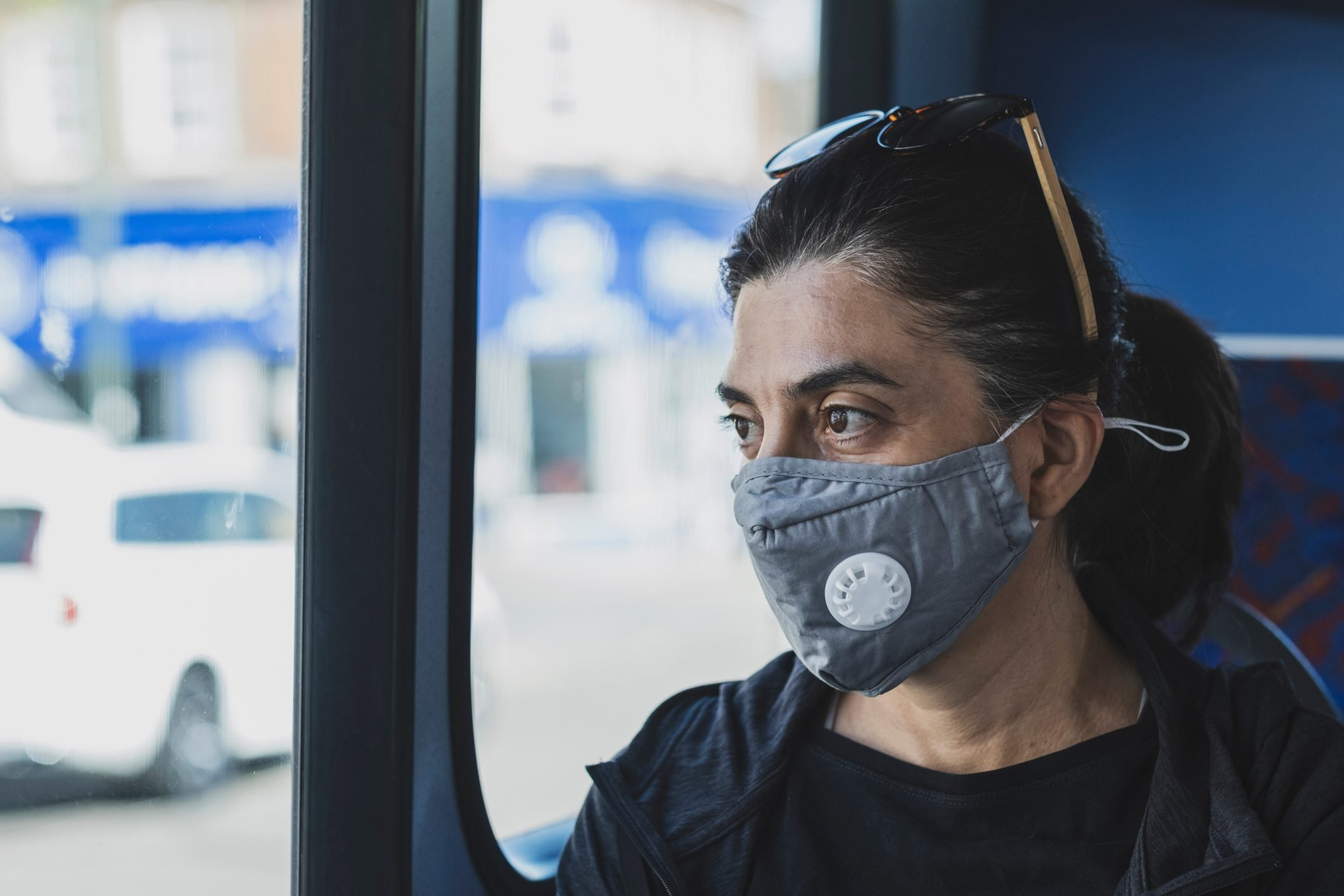 A woman on a bus using a protective mask