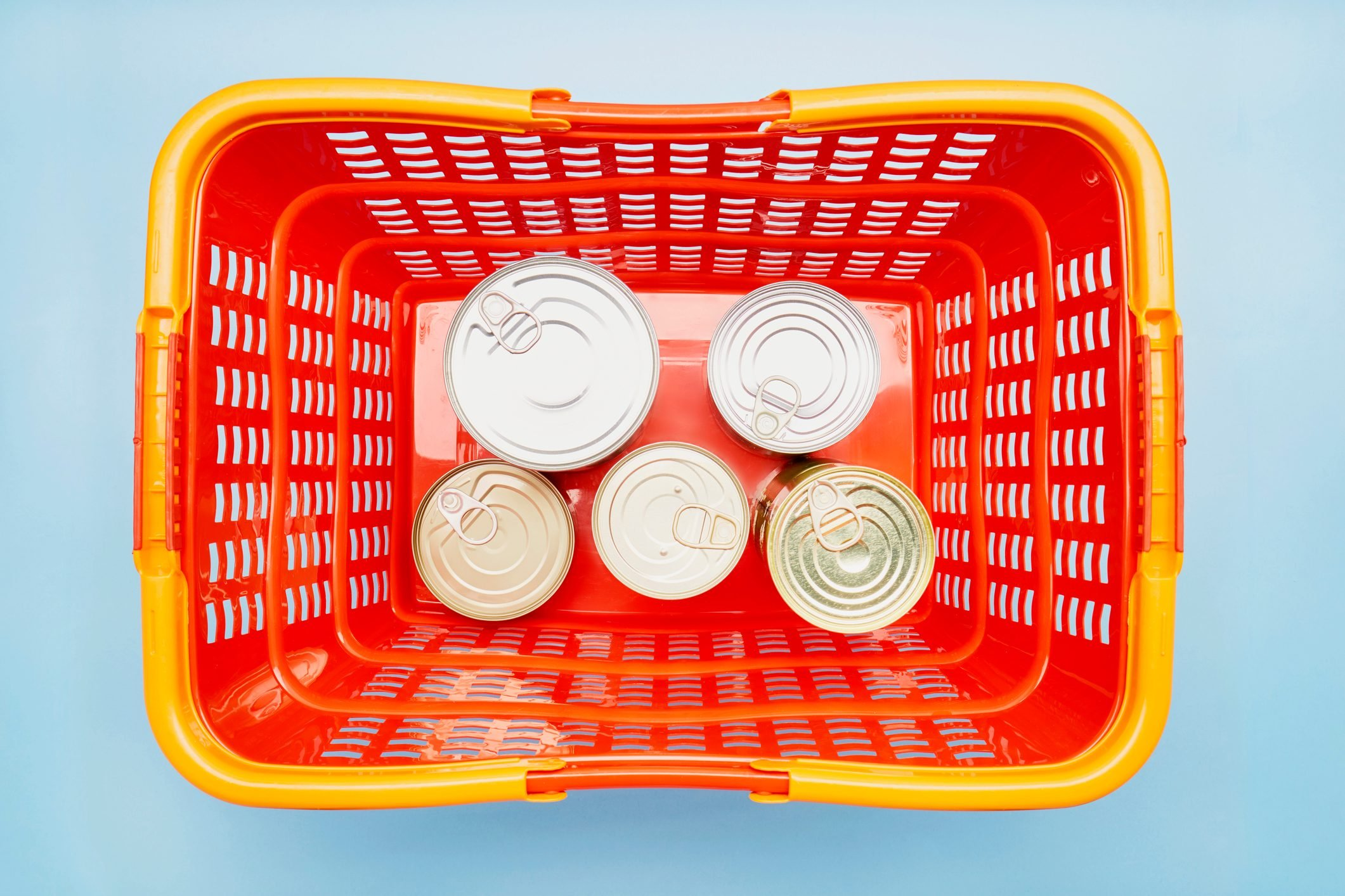 Still life of canned food in red shopping basket on blue background