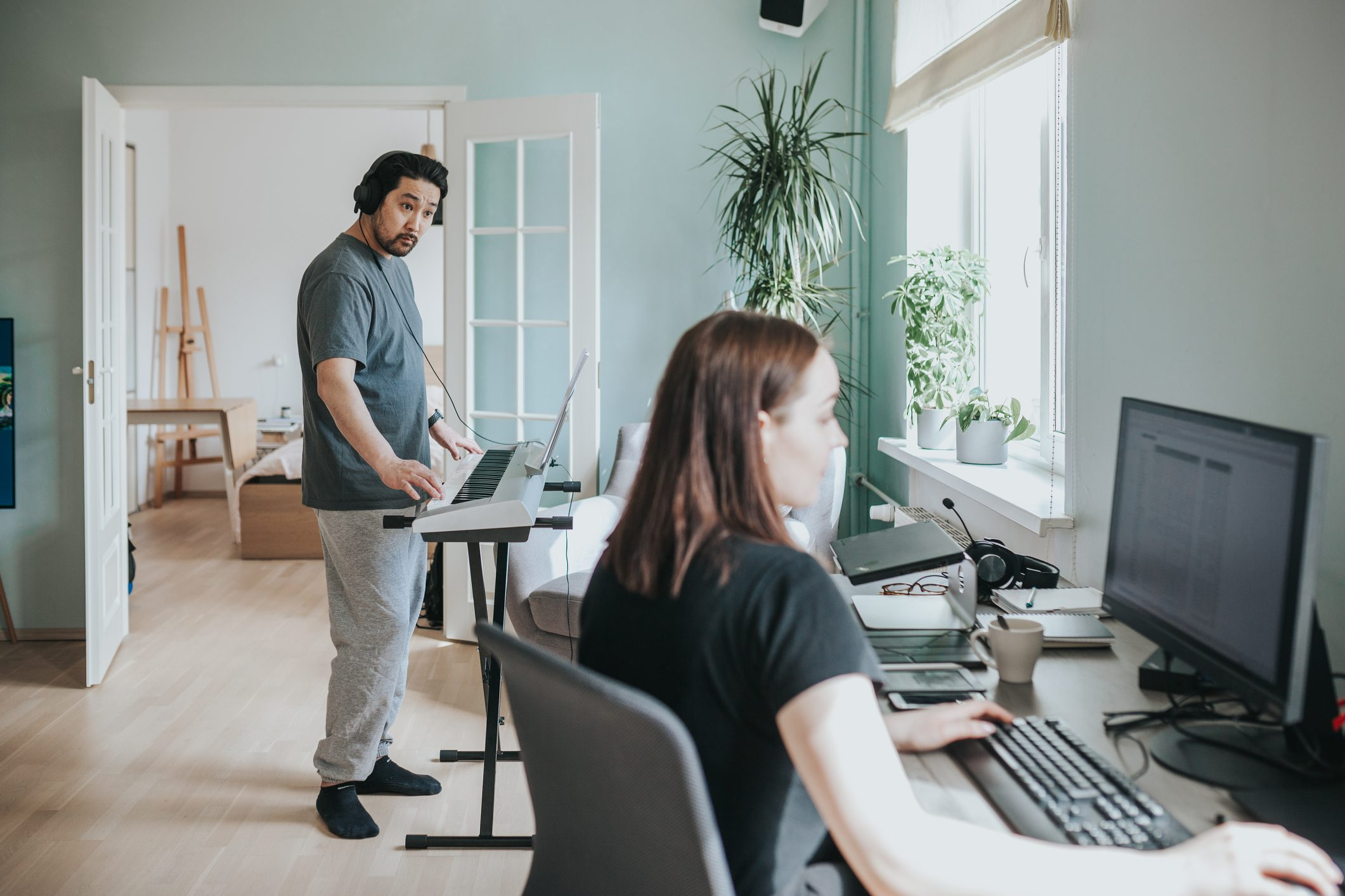 Asian adult man plays synthesizer while his wife is working at home