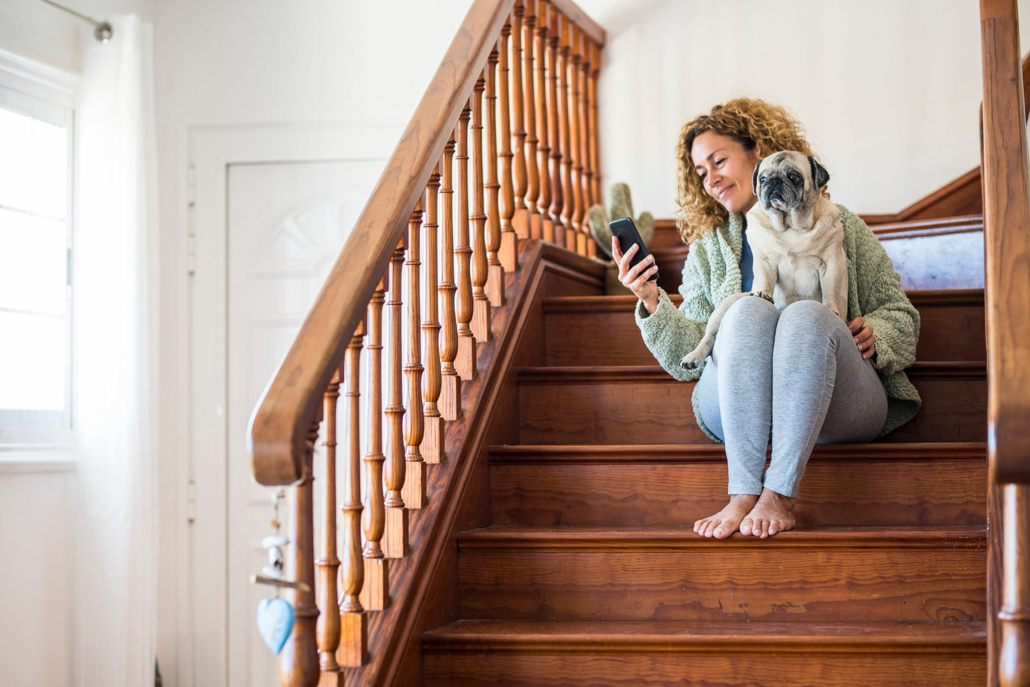 Woman sitting on stairs, using smartphone with pug on her lap
