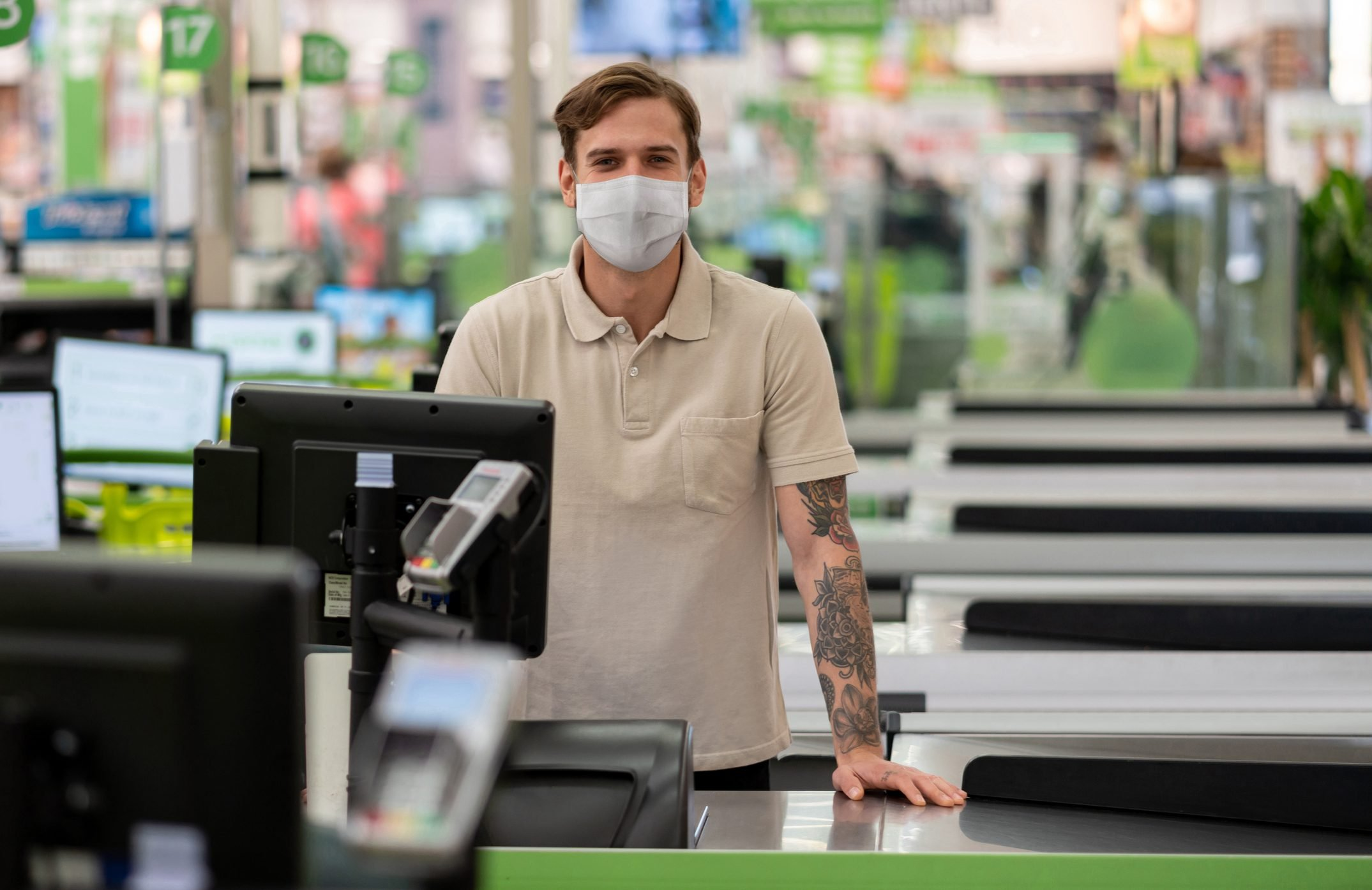 Cashier working at a supermarket wearing a facemask