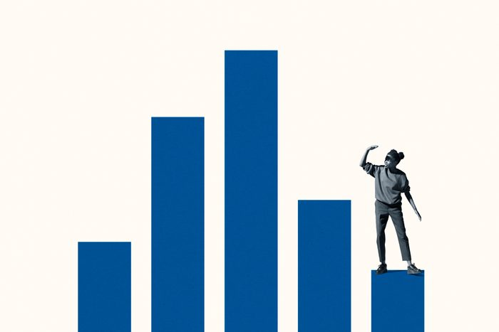 Woman shielding eyes while standing on bar graph