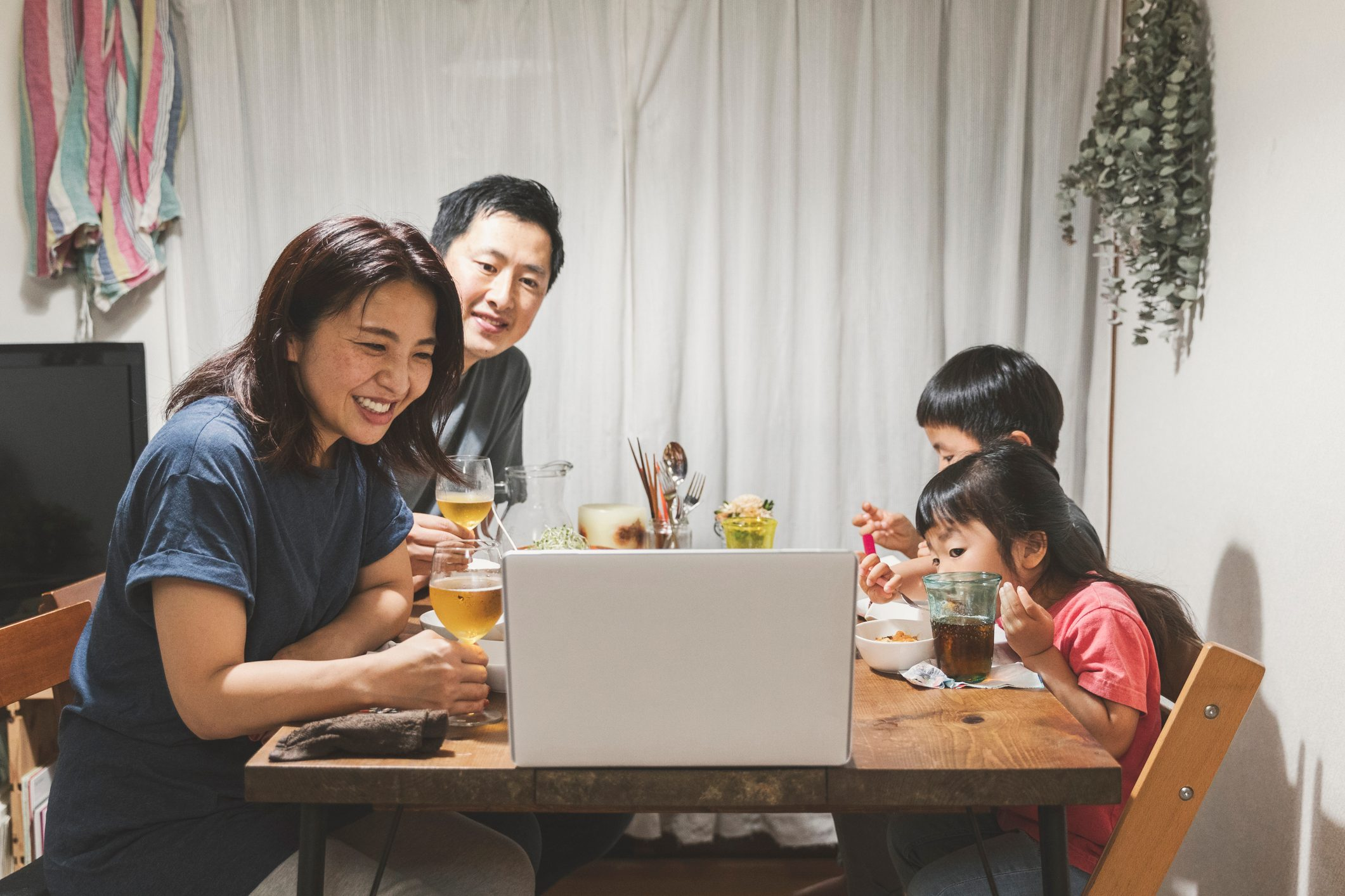 Family attending online video meeting and having dinner together at home