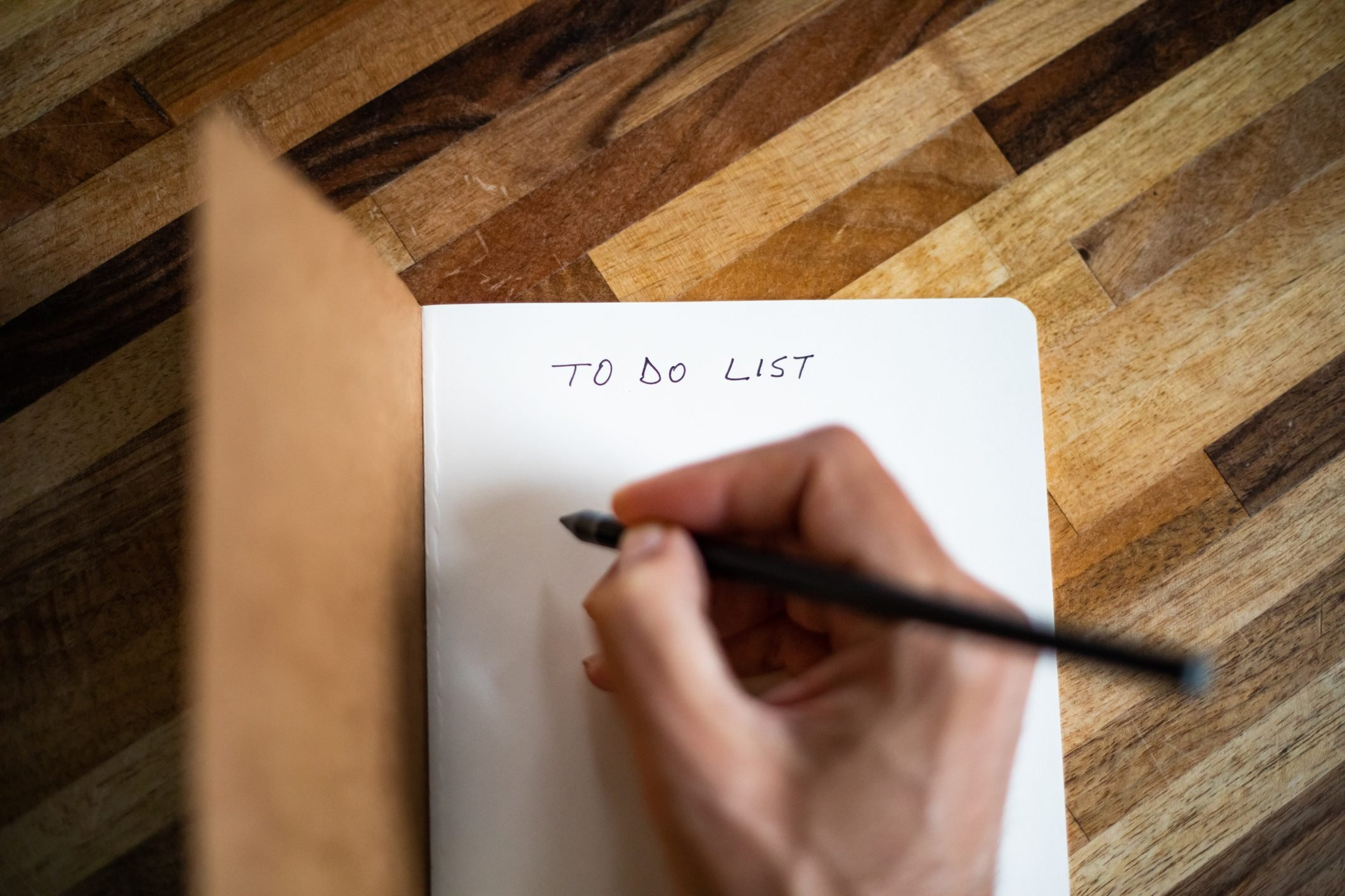 A person writing a to do list on a notebook