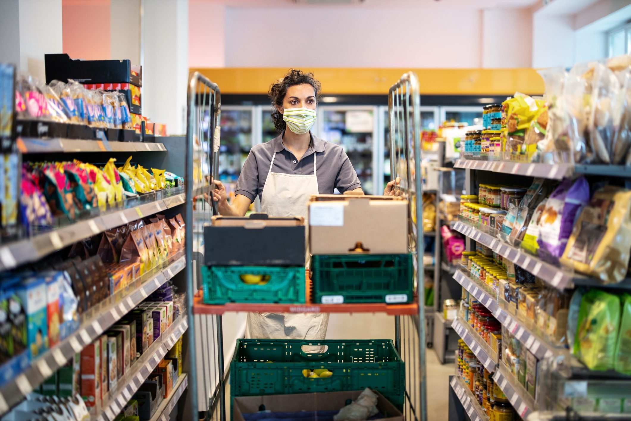 Female staff working in grocery store re-stocking goods